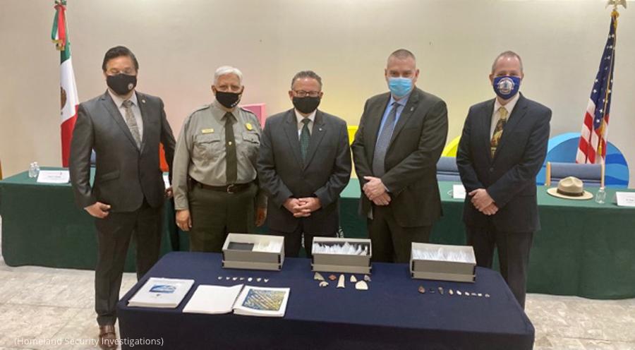 Homens em volta de uma mesa exibindo artefatos mexicanos (Divisão de Investigações de Segurança Interna)