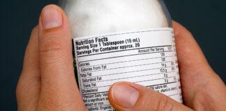 دستانی که شیشه و برچسب اطلاعات غذایی آن را در دست دارد (© Shutterstock)
