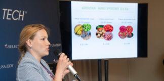 Une femme, micro à la main, en train de parler, et un écran diffusant des photos de fruits et légumes à côté d'elle (© Risdon Photography)
