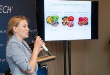 Woman speaking into microphone with photos of vegetables and fruits beside her (©Risdon Photography)