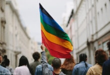 Rear view of people with rainbow flag (© Jacob Lund/Shutterstock)