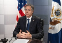 Secretary Blinken sitting in front of flags (State Dept./Freddie Everett)