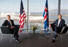 Deux hommes assis avec des drapeaux entre leurs chaises (© Saul Loeb/AP Images)