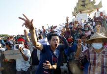 Hombre joven gritando y gesticulando frente a una gran multitud de gente que se manifiesta en Birmania (© AP Images)