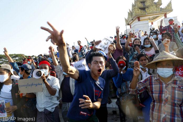 Jovem gritando e gesticulando na frente de uma grande multidão de pessoas protestando na Birmânia (© AP Images)
