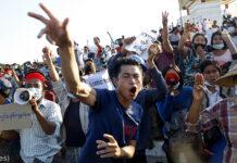 برما میں احتجاج کرنے والے ایک بڑے مجمے کے آگے ایک نوجوان چلا رہا ہے اور ہاتھ لہرا رہا ہے (© AP Images)'