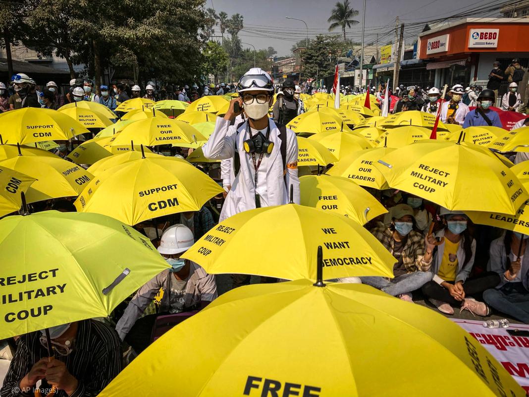 ہجوم کے درمیان ایک آدمی کھڑا ہے اور باقی لوگ زرد رنگ کی چھتریاں لیے بیٹھے ہیں  (© AP Images)
