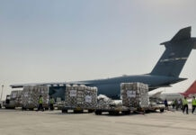Plane on tarmac next to large bundles of supplies on trailers (Nicholas Geboy/USAID)