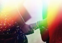 Two people holding hands with rainbow colors superimposed (State Dept.)