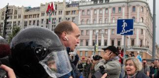 Polícia escoltando homem em meio à multidão na rua de uma cidade (© Alexander Zemlianichenko/AP Images)