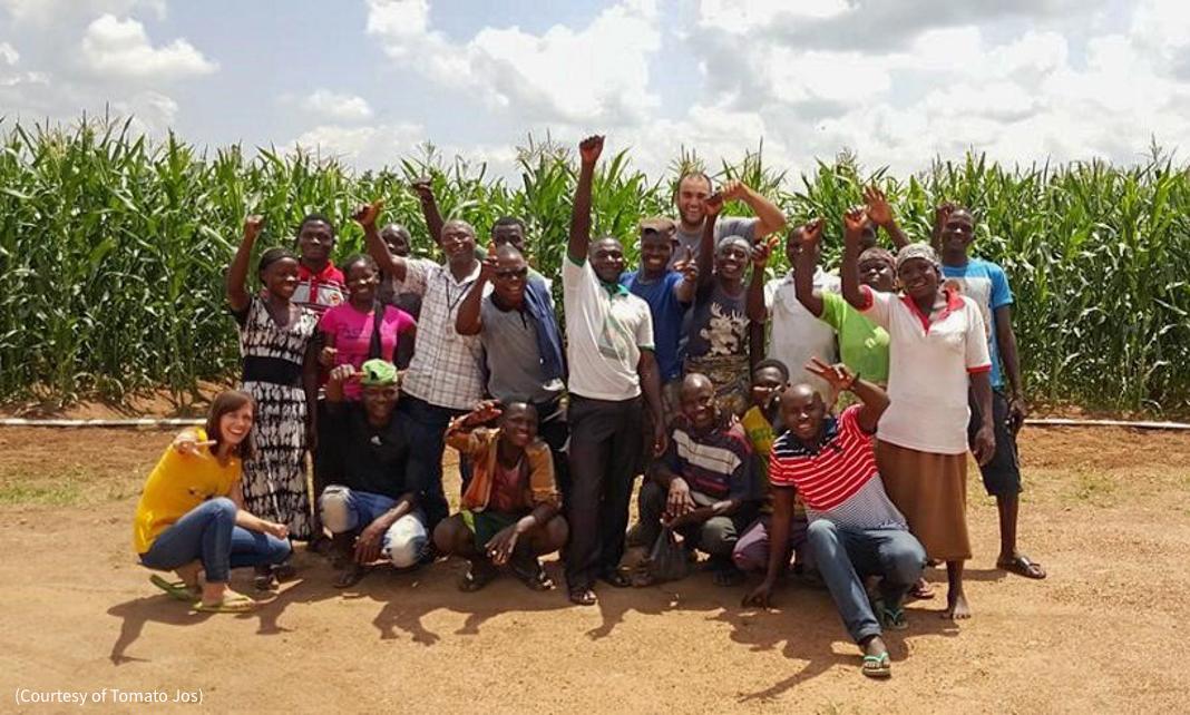 Группа людей позирует для фото на фоне сельскохозяйственных культур (Courtesy of Tomato Jos)