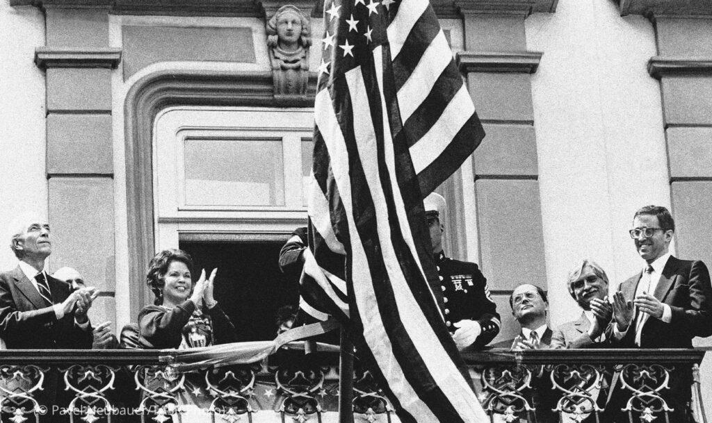 Ľudia tlieskajú pri vztyčovaní americkej vlajky na balkóne (© Pavel Neubauer/TASR Photo)