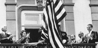 People clapping as U.S. flag is raised on a balcony (© Pavel Neubauer/TASR Photo)