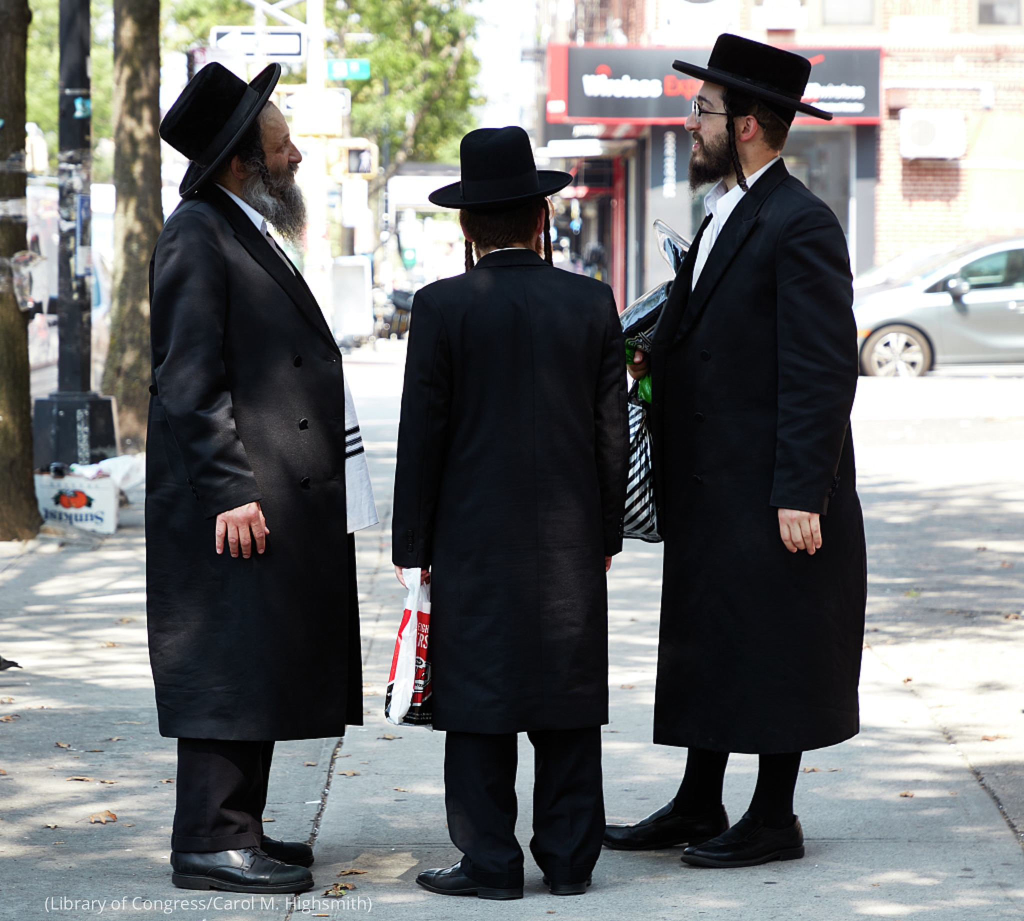 Three men dressed in black with beards, long coats, black hats, and side locks in their hair, talking on a New York street (Library of Congress/Carol M. Highsmith)