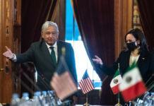 Андрес Мануэль Лопес Обрадор и Камала Харрис жестикулируют у стола с маленькими флагами США и Мексики (© Jacquelyn Martin/AP Images)