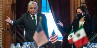 آندریس مینوئل لوپیز اوبریڈو اور کملا ہیریس اُس میز کے قریب کھڑے اشارہ کر رہے ہیں جس پر امریکہ اور میکسیکو کے چھوٹے پرچم رکھے ہیں۔ (© Jacquelyn Martin/AP Images)