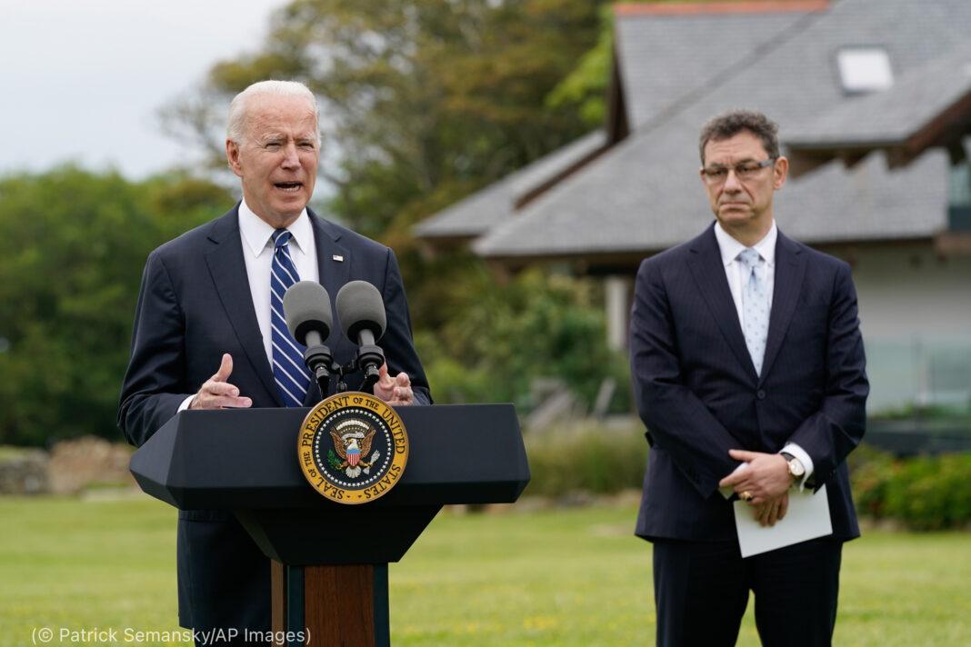 Joe Biden berbicara di podium luar ruangan dengan pria berdiri di sampingnya (© Patrick Semansky/AP Images)