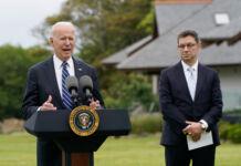 Joe Biden falando em uma tribuna ao ar livre; a seu lado, um homem em pé (© Patrick Semansky/AP Images)
