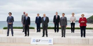 کاروباری لباس میں جی 7 رہنما ساحل سمندر پر لائن میں کھڑے ہیں (© Patrick Semansky/AP Images)