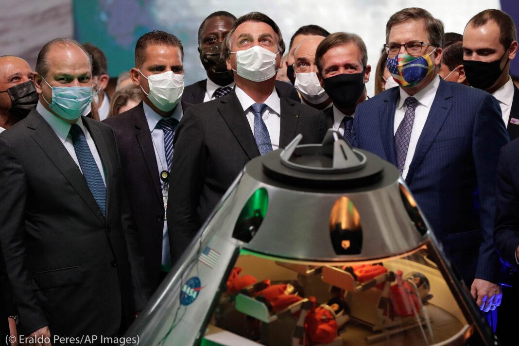 Мужчины стоят вокруг макета космической станции (©Eraldo Peres/AP Images)