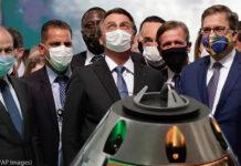 Homens em pé atrás de um modelo de módulo espacial (© Eraldo Peres/AP Images)