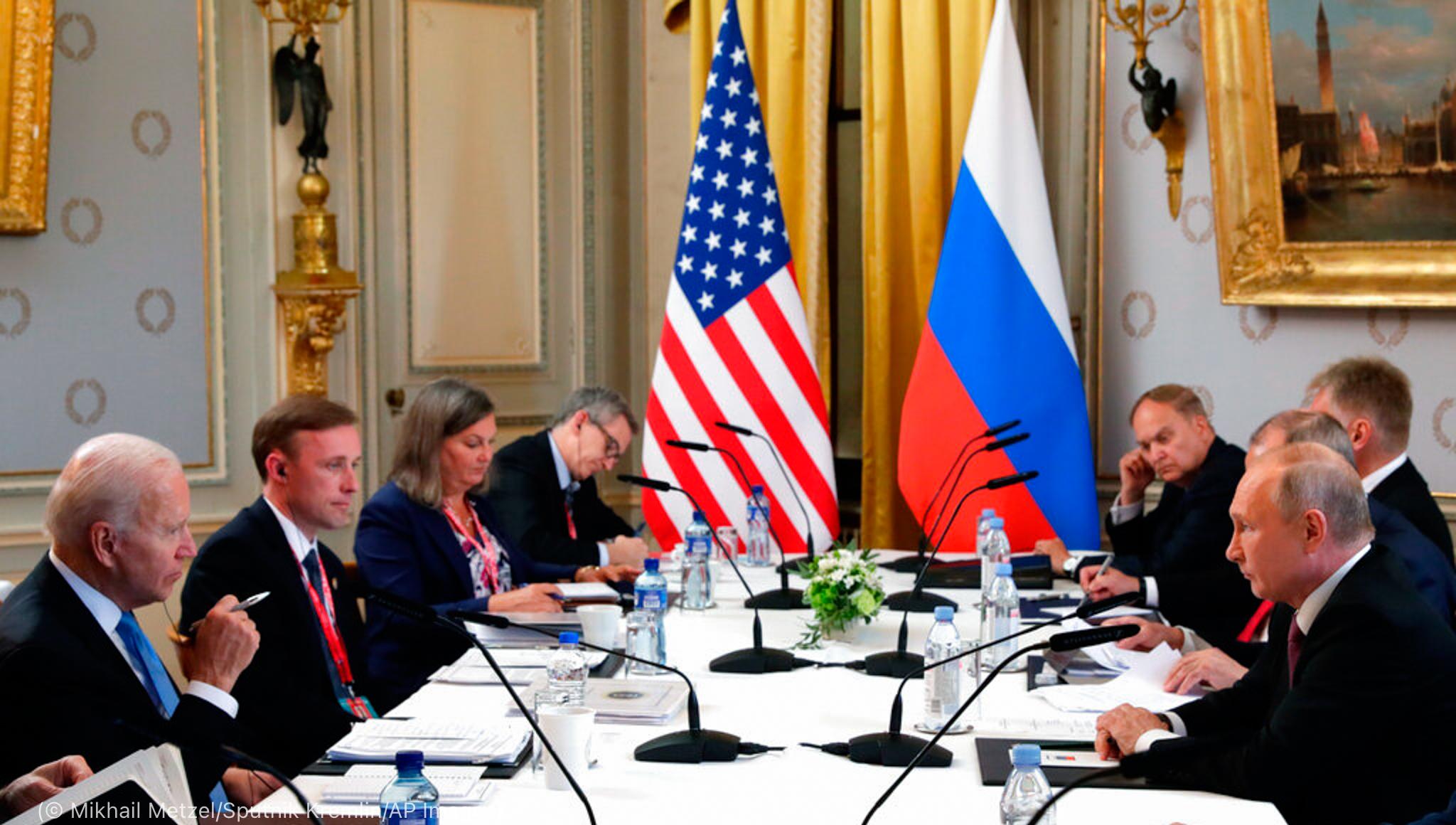 Joe Biden (au premier plan à gauche) et Vladimir Poutine (au premier plan à droite) à une table de travail avec d'autres personnes (© Mikhail Metzel/Sputnik Kremlin/AP Images)
