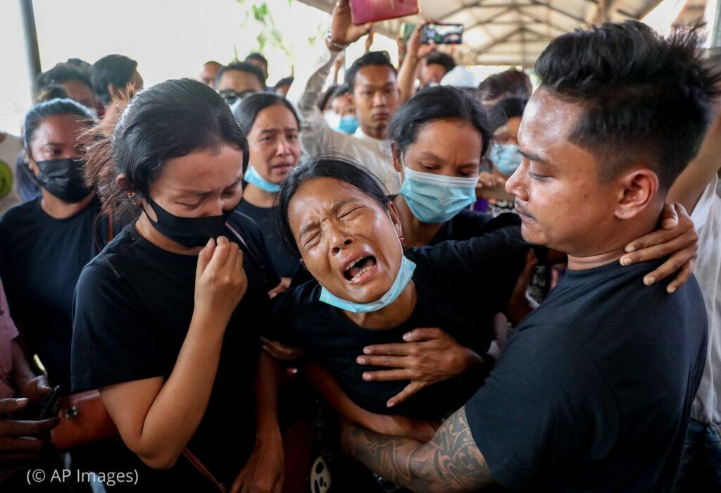 အခြားလူများက ကူညီပံ့ပိုးပေးစဉ် ငိုနေသော အမျိုးသမီး (ဓာတ်ပုံ - အေပီ)
