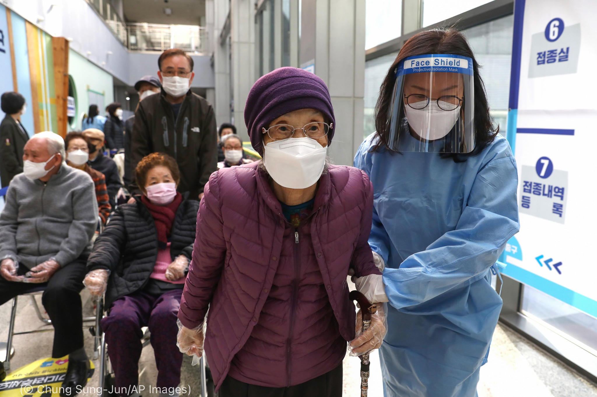 Health care worker in protective gear helping elderly woman to walk at front of long line in hall (© Chung Sung-Jun/AP Images)