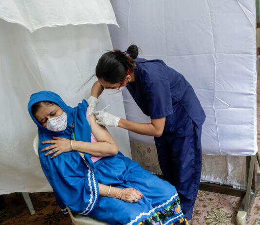 Perempuan divaksinasi sementara yang lainnya menunggu (© Rajanish Kakade/AP Images)