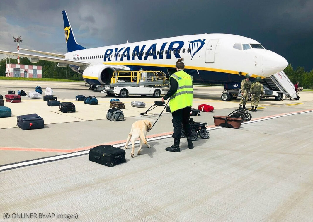 Man with dog on leash standing amidst luggage on tarmac in front of plane (© ONLINER.BY/AP Images)