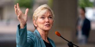 Jennifer Granholm gesturing while speaking into microphone (© Andrew Harnik/AP Images)