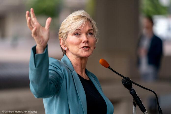 Jennifer Granholm gesticulando enquanto fala ao microfone (© Andrew Harnik/AP Images)