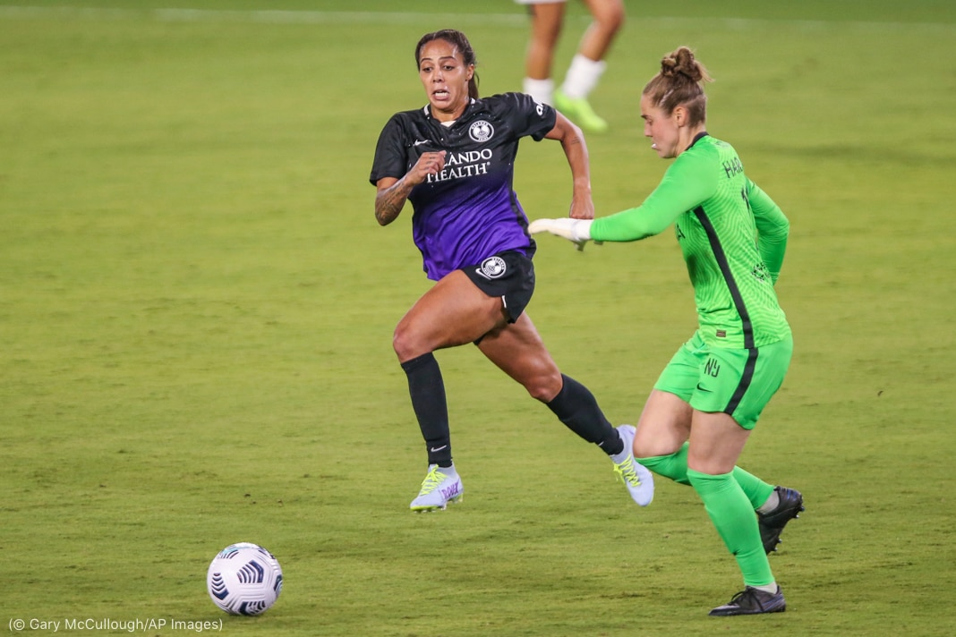Dos mujeres corren hacia un balón de fútbol (© Gary McCullough/AP Images)