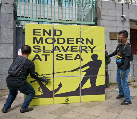 Мужчины с плакатами против рабского труда в рыболовной отрасли (© Bay Ismoyo/AFP/Getty Images)