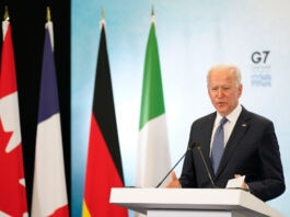 President Joe Biden speaking on podium with G7 logo behind him and next to Canadian, French, German and Italian flags (© Patrick Semansky/AP Images)