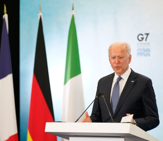 صدر بائیڈن جی 7 کے امتیازی نشان کے سامنے سٹیج پر کھڑے تقریر کر رہے ہیں اور دوسری طرف چار جھنڈے دکھائی دے رہے ہیں۔ (© Patrick Semansky/AP Images)