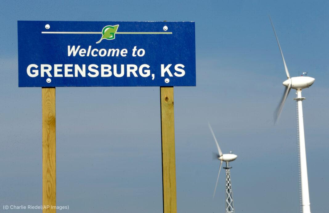 Cartel de 'Bienvenido a Greensburg, Kansas' junto a dos turbinas eólicas (© Charlie Riedel/AP Images)