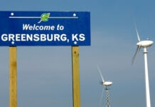 'Welcome to Greensburg, Kansas,' sign next to two wind turbines (© Charlie Riedel/AP Images)
