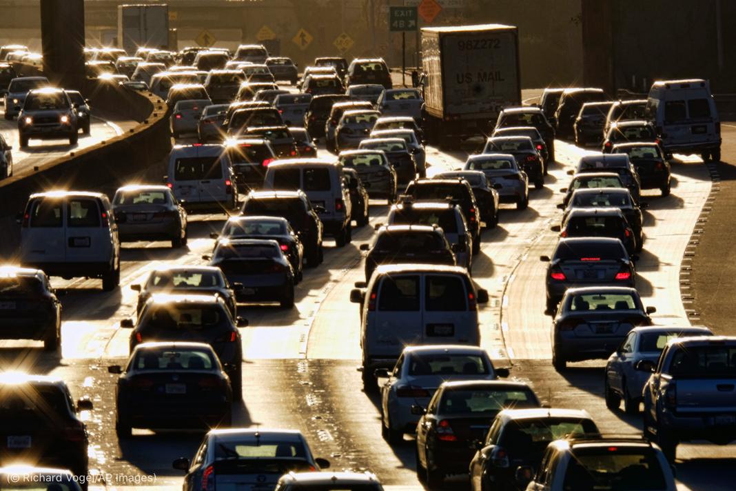 Múltiples carriles de vehículos en un tráfico congestionado que refleja la luz solar (© Richard Vogel/AP Images)
