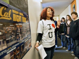 Молодая женщина разговаривает с группой людей (© Ray Chavez/The Oakland Tribune/Alamy)
