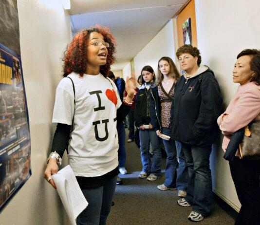 ایک نوجوان خاتون ایک گروپ میں شامل لوگوں سے باتیں کر رہی ہیں۔ (© Ray Chavez/The Oakland Tribune/Alamy)