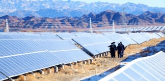 Group of people walking among solar panels near mountainous area (© Costfoto/Barcroft Media/Getty Images)