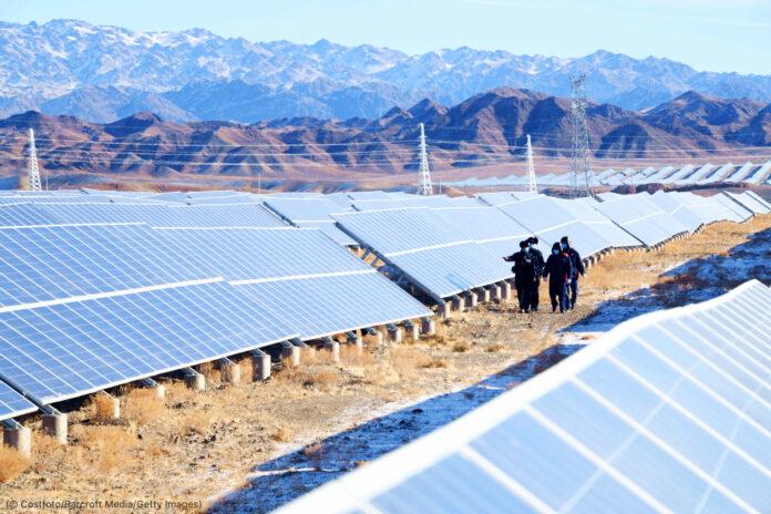 Grupo de pessoas caminhando entre painéis solares perto de área montanhosa (© Costfoto/Barcroft Media/Getty Images)