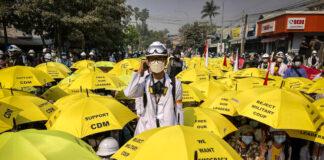 အဝါရောင် ထီးများဖြင့် ထိုင်နေသော လူအုပ်အလယ်တွင် မတ်တတ်ရပ်နေသော လူ (ဓာတ်ပုံ - အေပီ)