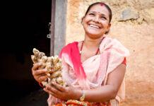 Mujer sosteniendo jengibre y sonriendo (USAID NEAT)