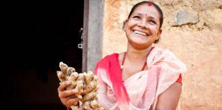 ہاتھوں میں ادرک اٹھائے ہوئے مسکراتی ہوئی ایک عورت (USAID NEAT)