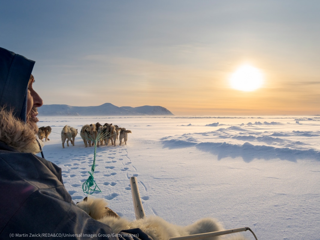 Person on dog sled surrounded by ice and snow (© Martin Zwick/REDA&CO/Universal Images Group/Getty Images)