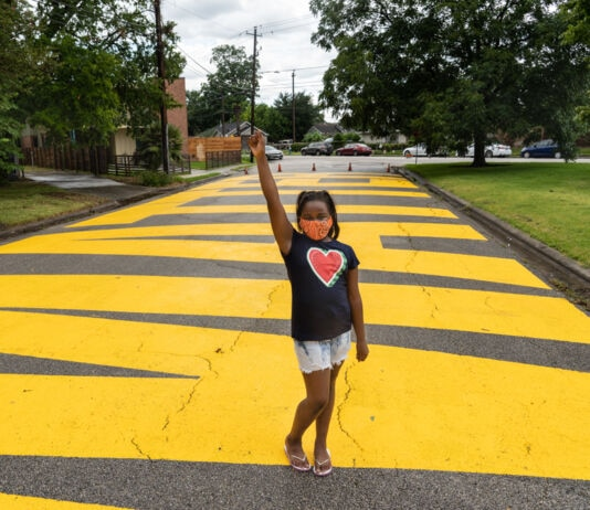 Young girl standing on yellow words painted on road, raising her arm and wearing shirt with heart on it (© Go Nakamura/Getty Images)