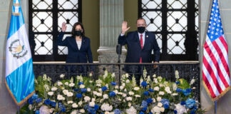Kamala Harris and Alejandro Giammattei waving from balcony, with Guatemalan flag and U.S. flag on either side (© Jacquelyn Martin/AP Images)
