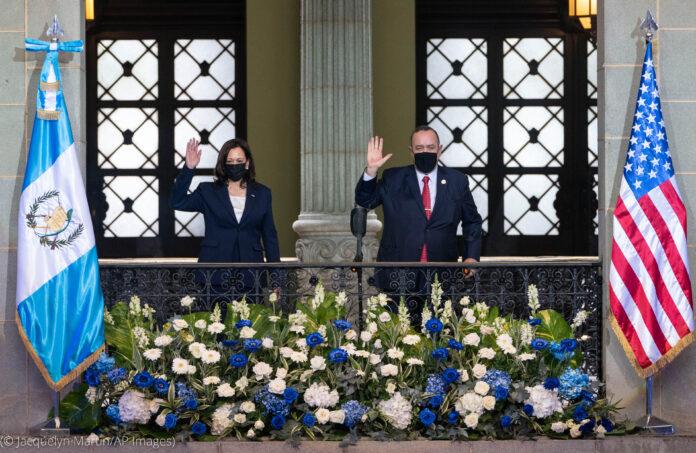 Kamala Harris y Alejandro Giammattei saludan desde un balcón con las banderas de Guatemala y de Estados Unidos a los lados (© Jacquelyn Martin/AP Images)